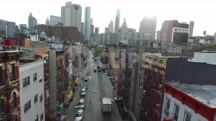 aerial over Chinatown street with skyscrapers in background in Lower Manhattan NYC
