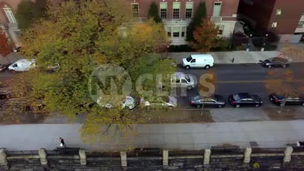 aerial of van driving in Harlem zooming out to buildings on sunny day in NYC
