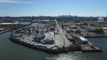 aerial waterfront where Brooklyn meets Queens - Manhattan skyline in far distance in NYC