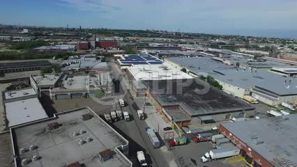 aerial of warehouses in the Bronx panning to Manhattan skyline in distance over river water in NYC