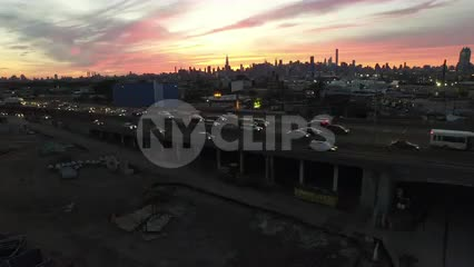 high view of cars driving in traffic on the highway with beautiful Manhattan skyline at sunset