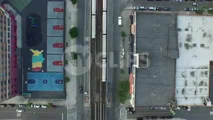 aerial over 1 train running into tunnel - uptown and downtown trains crossing paths on elevated track running through Harlem from overhead view