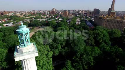 aerial of Prison Ships Martyrs' monument - circling Fort Greene Park in Brooklyn with trees and Manhattan skyline with buildings and skyscrapers in background