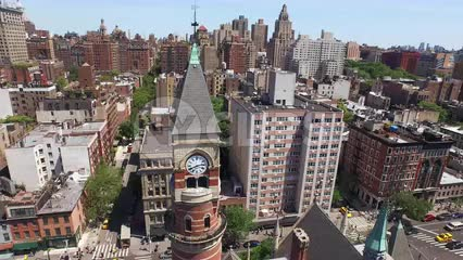 circling the Jefferson Market Library - aerial of landmark clock tower in Greenwich Village with Manhattan skyscrapers in background on sunny day