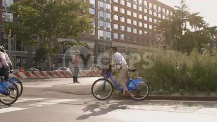 hipster on Citi Bike and yellow taxi cab driving in Greenwich Village on sunny day in summer