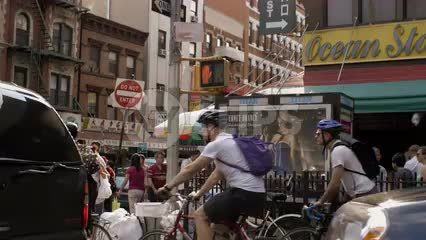 bicyclists in Chinatown on bright sunny day - people crossing street in summer