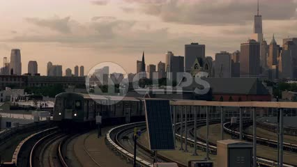 G train arriving at Smith-Ninth Street elevated subway station in Brooklyn with Manhattan skyline in background at sunset in NYC