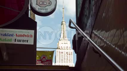 Empire State Building view coming out of 34th street subway station stairs on sunny day