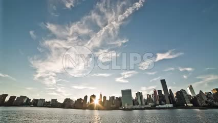 Manhattanhenge - view of Manhattan skyline at sunset from across East River - sun beaming through buildings as it dips