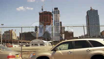 cars driving along Westside Highway past fence and construction site with developments - 4K in Manhattan NYC