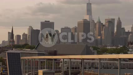 subway F train arriving at Smith-9th Streets elevated outdoor station in Brooklyn with Freedom Tower in Manhattan skyline in background