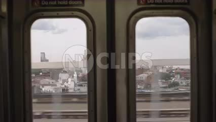 window view from elevated subway train slowing down and stopping in Brooklyn NYC
