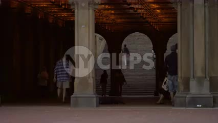 people walking under Bethesda Terrace in Central Park on summer day in NYC