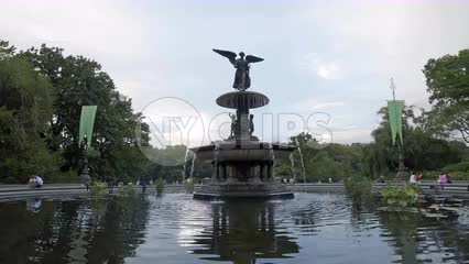 Bethesda Statue with fountain water sprinkler and ripples in pond in Central Park on summer day in NYC