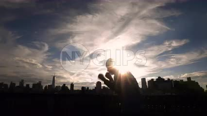 silhouette of man boxing on New York City rooftop with Manhattan skyline at sunset