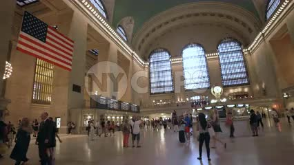 interior Grand Central Station in summer - big American flag in large terminal room with Metro North schedule information