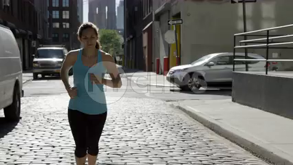 athletic woman jogging in Brooklyn on cobblestone street - 4K in slow motion NYC