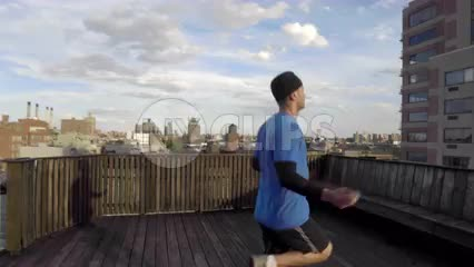 man jumping rope - athlete exercising with jump rope on roof top in with Manhattan skyline view on summer day in NYC