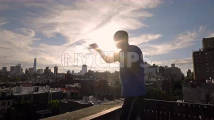 man sparring on rooftop with Manhattan skyline at sunset in NYC