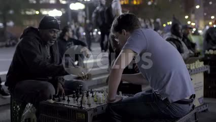 old black man and young white kid playing chess outside in Union Square at night in NYC