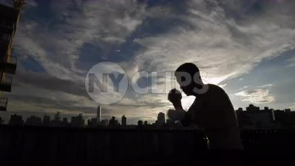 silhouette of man sparring on rooftop at sunset with Manhattan skyline in background in NYC