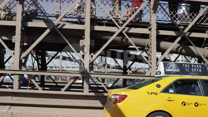 driving across Brooklyn Bridge - taxi cab crossing alongside driver's side pov with people walking on pedestrian path in 4K NYC