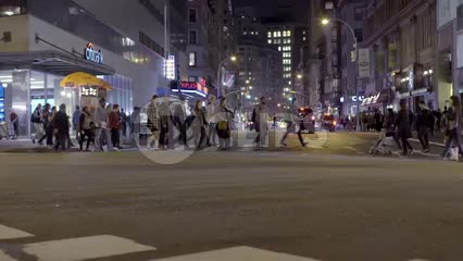 crowded crosswalk at Union Square at night - people crossing street in slow motion in New York City