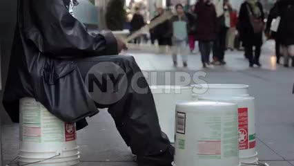 drummer playing in street on buckets on cold winter day in New York City