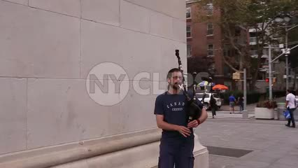 man playing bagpipes in Washington Square Park on summer day