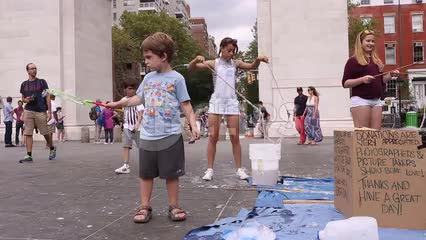 kids playing with bubbles in Washington Square Park on summer day in NYC