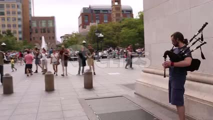 street musician playing bagpipes in Washington Square Park on summer day in NYC