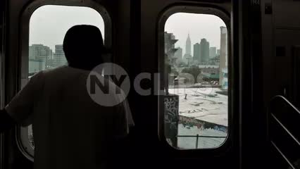 silhouette of man in baseball cap riding elevated subway train in Queens in NYC