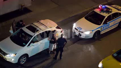 police officer talking to man at night - overhead view - flashing turret lights on cop car