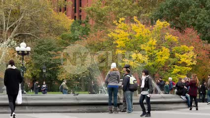 Washington Square Park in fall with beautiful colored leaves on trees - colorful shot of people and fountain spraying water