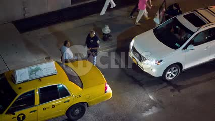 taxi cab driver and police officer having conversation on street at night