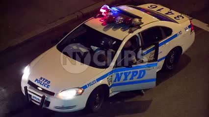 police from overhead view - officer getting out of NYPD car with flashing turret lights in street at night
