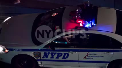 overhead view of flashing turret lights on cop car - NYPD police vehicle driving at night