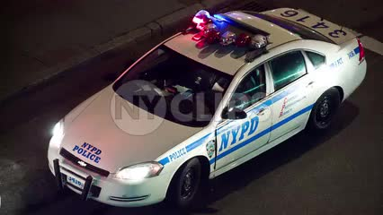 NYPD police car with flashing turret lights double parked in street at night with tourism bus driving by