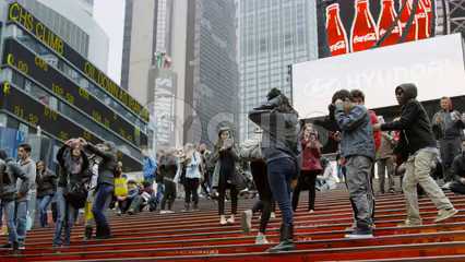 red stairs in Times Square crowded with kids posing for pictures - tourists visiting New York City on cold winter day in 4K slow motion
