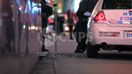 police hanging out leaning on NYPD car in Times Square at night in New York City