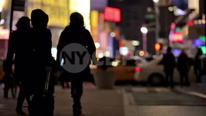 silhouettes walking in Times Square at night in winter - three women with luggage - tourists in Manhattan