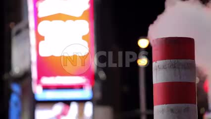 noisy Times Square at night with construction pipe blowing smoke - steam