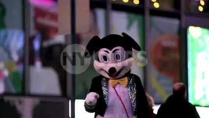 Times Square performer in Mickey Mouse costume on street at night