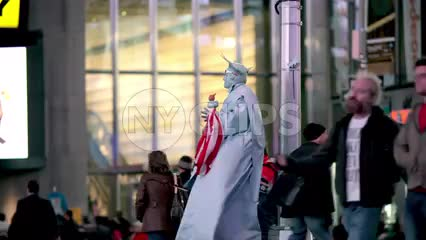 Statue of Liberty performer in costume in Times Square on windy fall night in NYC