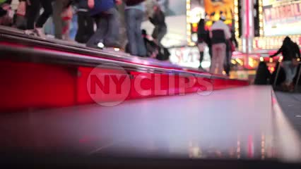 famous red steps in Times Square at night - tourists speaking different languages