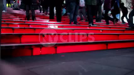 woman with high heels walking up famous red steps in Times Square at night