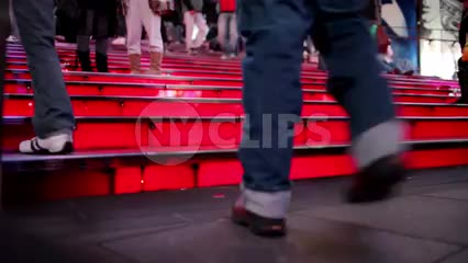 Times Square red steps with close-up of feet walking up stairs
