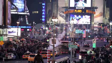 high view of Times Square at night with construction pipe blowing smoke