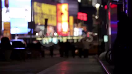 silhouettes of people walking and cars passing in Times Square at night