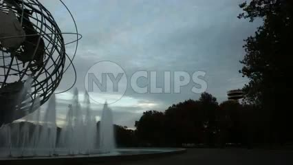 panning across globe sculpture in Flushing Meadows Corona Park with water sprinklers in Queens New York at beautiful sunset in early evening